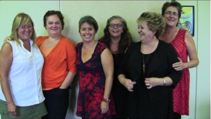 6 femmes debout dans une ligne, souriantes